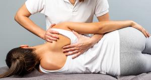 Quiroprático ajuda a melhorar a coluna de mulher que está deitada.