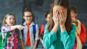 Meninos fazem bullying a uma criança que chora desconsolada.
