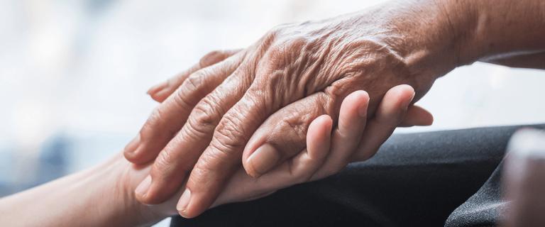Jovem e idosa dão as mãos.