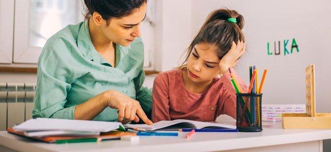 Mãe ajuda a sua filha com dificuldades de aprendizagem.